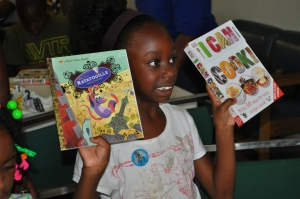 A child shows off her free books from the book give-away.