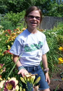 Grand Rapids Junior Master student shows off a flower at a Kent County Master Gardener's home daylily garden in July 2011.