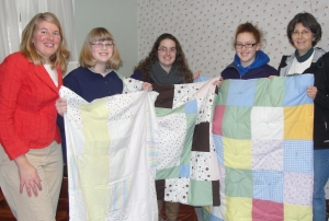 MSU Extension Chippewa County 4-H program instructor Andrea Caron, 4-H members, and 4-H club leader Sherry Duesing display quilts that the three 4-H members made and donated.