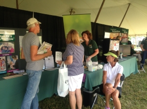 Michigan State University Extension staff members Joyce McGarry (green shirt) and Beth Jabin (white shirt), interact with Ag Expo attendees