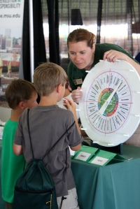 Michigan State University Extension educator Sara Keinath explains the 4-H life-skills wheel to two young attendees of Ag Expo.
