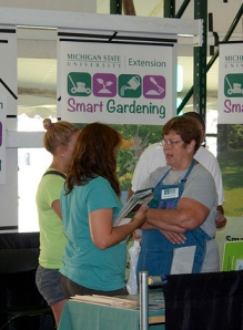 Michigan State University Extension Master Gardener Marianna Foster (right) gives attendees tips on smart gardening at Ag Expo.