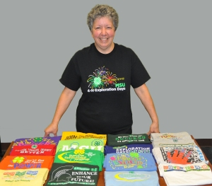 MSU ANR Communications graphic artist Marian Reiter in one of her 4-H Exploration Days T-shirt designs, poses in front of some of the many T-shirts she designed for the annual event.