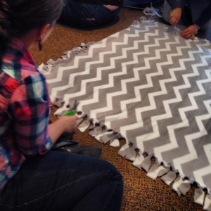 "A volunteer makes a blanket at the ""Live in Laughter & Warm the Heart"" Martin Luther King (MLK) Day of Service event on Jan. 18, 2014"