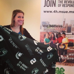 Kristi Bowers, Michigan State University (MSU) Extension Kent County 4-H program coordinator, poses with an MSU blanket