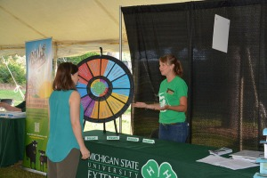 Michigan State University Extension educator Makena Schultz interests a visitor in the Targeting 4-H Life Skills Interactive Educational Display wheel at Ag Expo