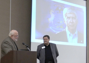 MSU CANR Dean Fred Poston (left) reads from the tribute letter presented to Dr. Chris Peterson, MSU Product Center director, (right) on behalf of Gov. Rick Snyder.