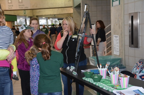 A group of sisters spin the wheel during a 4-H booth activity.