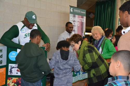 Photo of interactive booth with two 4-H staff members guiding youth and parents in a fun activity.