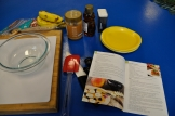 Photo with a recipe book, ingredients such as bananas, peanut butter, honey, setting up for a demonstration.