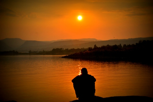 Person sitting looking out over a lake and hills orange with sunset light.