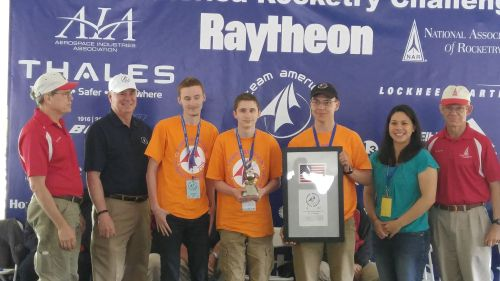 The Deford Dazzlers 4-H Club receives their award for finishing in second place in the nation during the Team America Rocketry Challenge. The team is in the orange shirts (from left to right): Peter Hansen, Alexander Hansen and Chrysler Parrish.