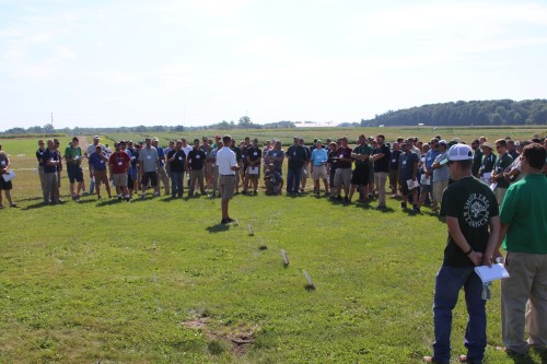 A crowd of participants listen to a demonstration in a field.