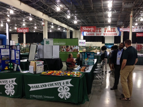 Photo of the Oakland County 4-H, MSU Extension, AgBioResearch and the College of Agriculture and Natural Resources booth. Several people standing and sitting and chatting.