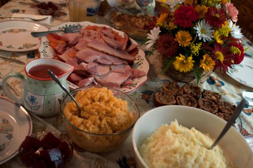 Photo of a table set with Thanksgiving dinner: squash, mashed potatos, ham, desert and flowers.