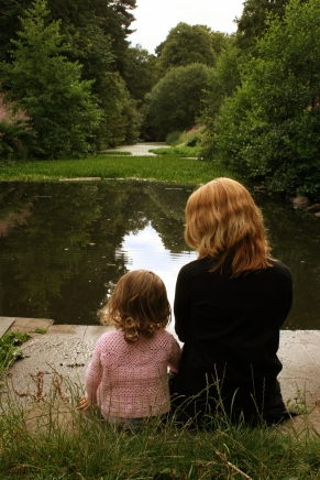 Mother a daughter sit and look at pond.