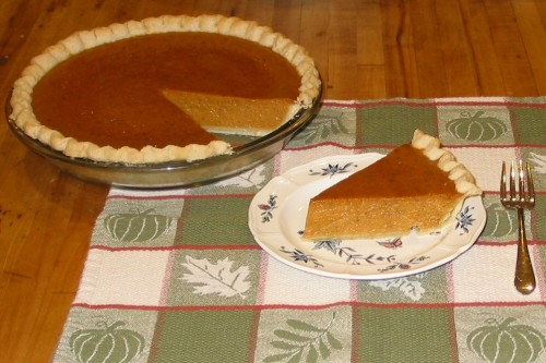 A pumpkin pie with a piece cut out and sitting on a dish.