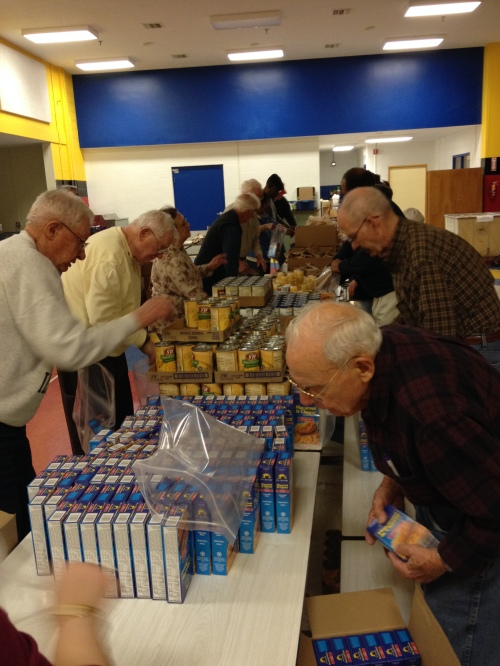 Volunteers put together survival kits of food for teh Weekend Survival Kit program.