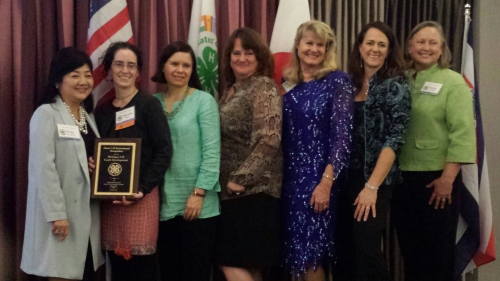 From left to right: Yoko Kawaguchi, Martha Shapton, Heather Gray, Gwen Apger, Jan Brinn, D'Ann Rohrer and Cathy Sutphin. Photo courtesy of D'ann Rohrer; all posing with the award plaque on stage.