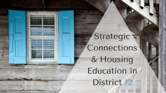"Photo of the side of a house that is made of gray wood with a stair case in front of it. The wall of the house has a window with blue shutters. Over top of the photo is the title of the blog post ""Strategic Connections & Housing Education in District 12."""