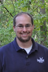 Headshot of Brandon Schroeder in front of green leaves, wearing a blue polo that says Sea Grant.