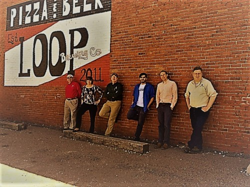 Mark Thomas, Kay Cummings, Andy Hayes, Khurram Imam, Micah Loucks, and Frank Gublo pose for a photo in front the Loop Brewing Co. brick building.