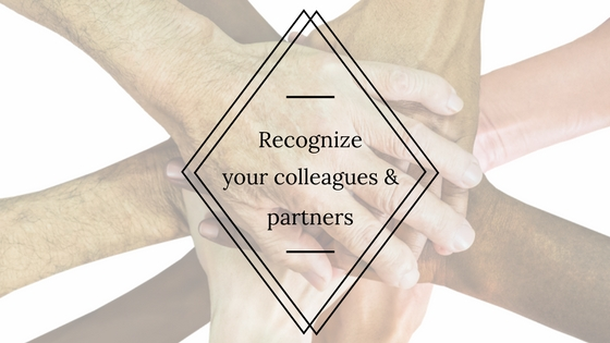 """Photo of hands on top of one another in a team huddle with the text overtop of the hands that reads, """"Recognize your colleagues and partners."""""""