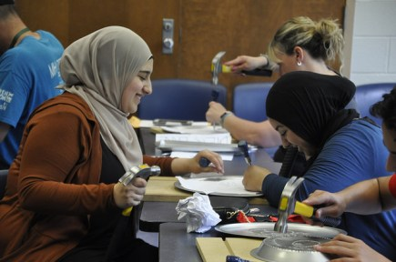 Students work on a project as part of one of the sessions with hammers.