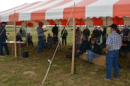 Participants listen at a session under a tent outdoors.