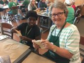 A grandmother and granddaughter stretch pizza dough.