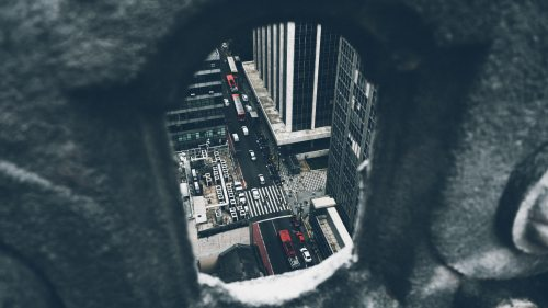 Photo of a city street looking through a small window.