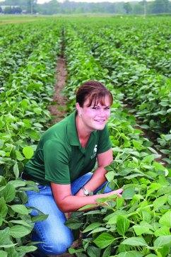 Christy kneels in a field of crops.